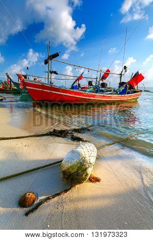 The Thai traditional fishing vessel is decorated with colourful tapes on the sandy beach with fishing tackles.