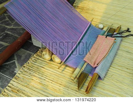 Traditional hand-weaving loom being used to make a fabric for cloth