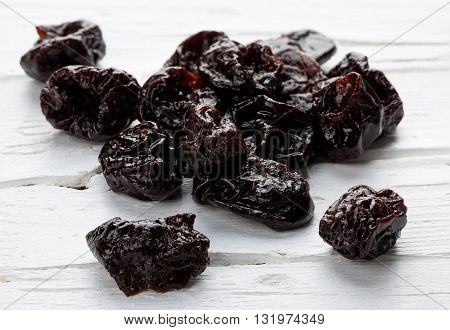 Dried plums on white wooden weathered background closeup.