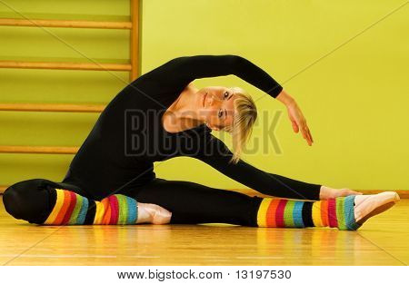 Ballet dancer doing stretching exercise on a floor