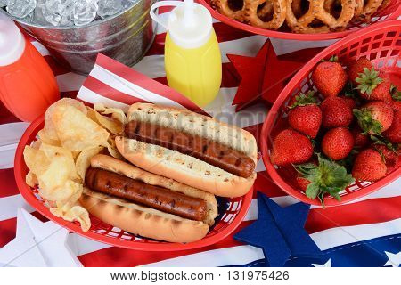 Looking down on a picnic table decorated for the 4th of July. Hot Dogs chips strawberries mustard ketchup pretzels and ice bucket fill the frame. Horizontal Format.