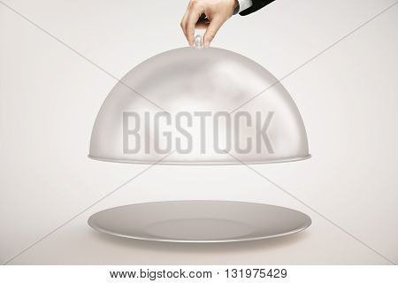 Man's hand opening silver cloche on light background. Mock up 3D Rendering