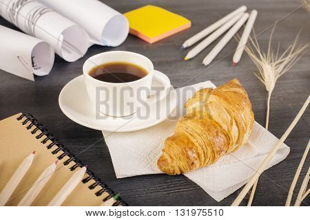 Closeup of wooden desktop with croissant coffee cup stationery wheat spikes and paper rolls