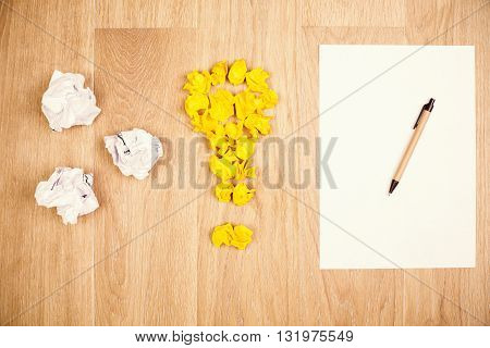 Idea concept with crumpled paper lightbulb and white sheet with pen on wooden desktop