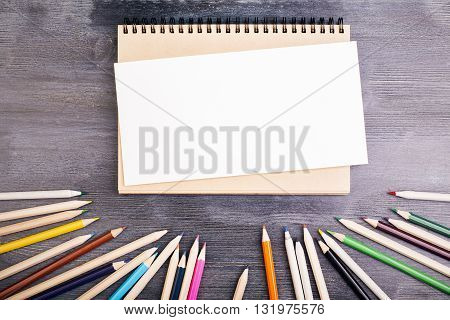 Top view of wooden desktop with blank paper notepad and colorful pencils. Mock up
