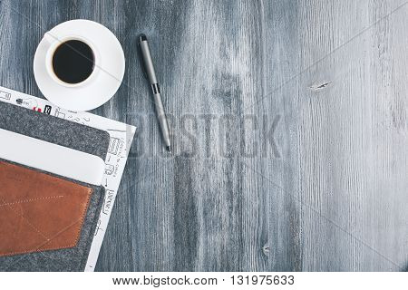 Top view of dark wooden desktop with coffee cup and saucer pen and laptop cover. Mock up