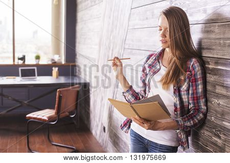 Thoughtful female in interior with notepad and pencil in hands
