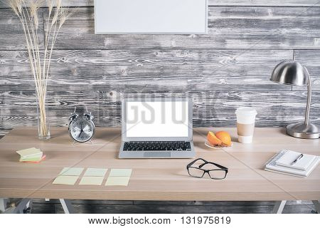 Creative designer desktop with blank white laptop screen alarm wheat spikes lamp coffee cup blank picture frames and many other items. Mock up