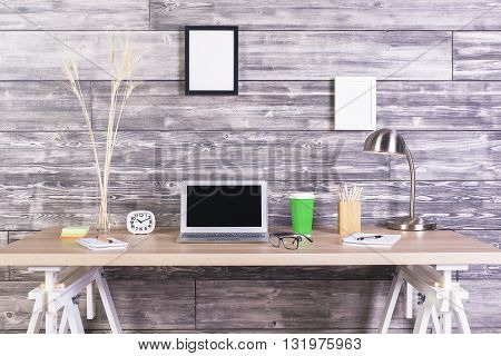 Creative designer tabletop with blank laptop clock coffee and other items with picture frames hanging above on wooden wall. Mock up