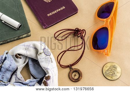 Travel concept with bandanna tinted glasses coins compass with string journal and passport objects on top of yellow surface