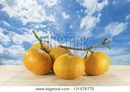 Sweet orange. Orange on the wooden table on the blue sky background