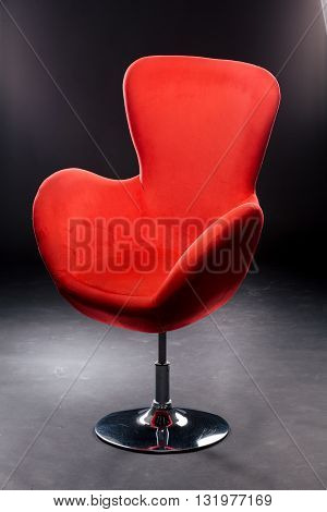 Red velour seat on the Nickel-plated steel leg in the Studio on a black background. Comfortable office chair red