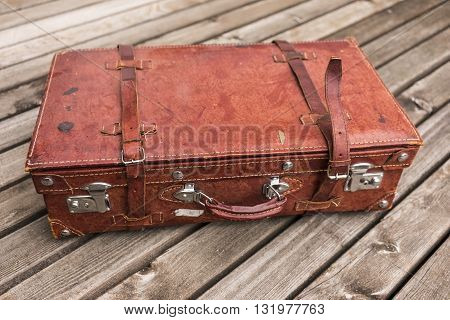 Old worn vintage brown leather suitcase with straps on a wooden deck in a travel and vacation concept