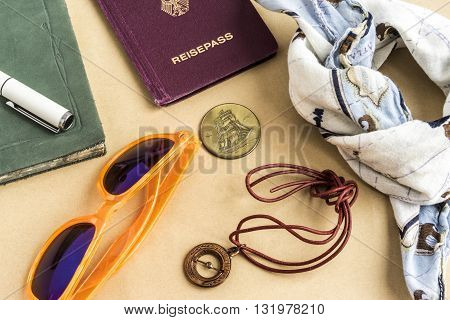 World travel concept with bandanna tinted glasses coins compass journal and passport objects on top of yellow surface