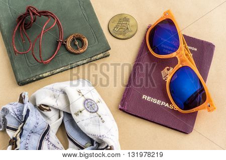 Tourist background theme with bandanna tinted glasses coins compass with string journal and passport objects on top of yellow surface