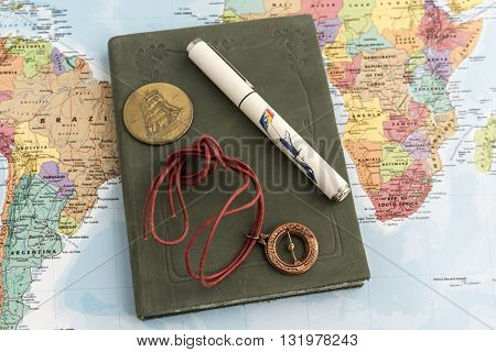 Green hard cover journal with pen stringed compass talisman and coin on top of map displaying South American and Africa