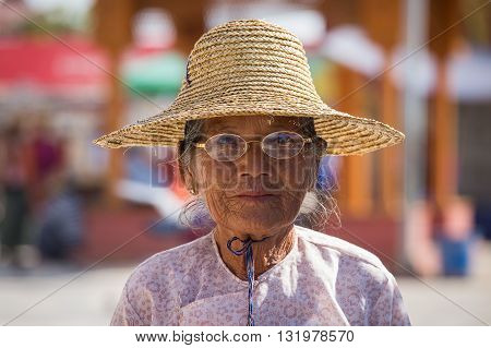 INLE LAKE MYANMAR - JANUARY 12 2016: Unidentified old woman in a straw hat . The local people are hospitable and friendly to tourists