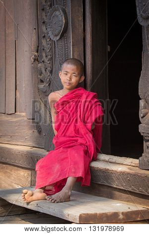 MANDALAY MYANMAR - JANUARY 17 2016 : Young monk sitting and looking at Shwenandaw Monastery is built in the traditional Burmese architectural style