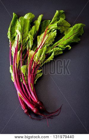 Beet leaves on black stone table view from above.