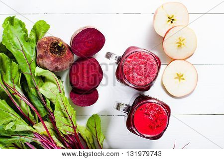 Red smoothies from beetroot beet leaves and apple on white wooden table. Flat lay.