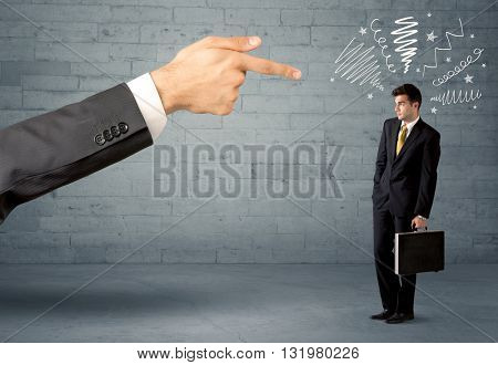 Boss firing employee concept with a huge hand pointing at confused business person illustrated by drawn lines in front of grey brick wall