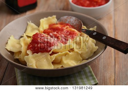 Finnish ravioli with shredded Parmesan cheese and tomato sauce