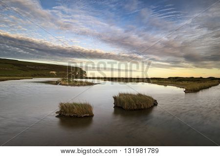 Landscape Image Of Tidal Pool At Coast During Evening With Dramatic Sky