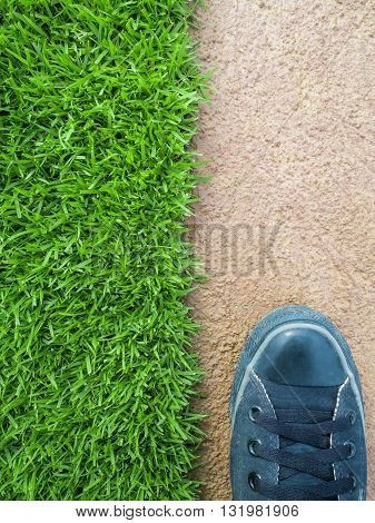 Top View of One Feet Standing on the Lawn Between the Cement Floor Nature or Building Concept Nature or Man Made Concept Copy Space Vertical
