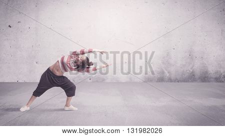 A beautiful young hip hop dancer dancing contemporary urban street dance in empty clear grey wall background concept.