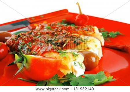 cheese cannelloni served with pepper and tomato on red plate . shallow dof