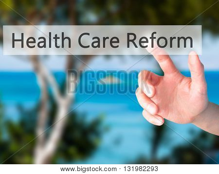 Health Care Reform - Hand Pressing A Button On Blurred Background Concept On Visual Screen.