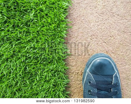 Top View of One Feet Standing on the Lawn Between the Cement Floor Nature or Building Concept Nature or Man Made Concept Copy Space Horizontal
