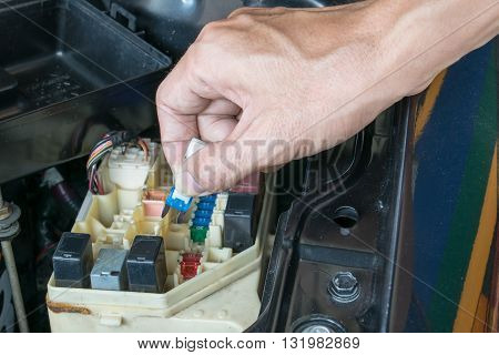Auto mechanic checking a car fuse. car, fuse, automotive, electronics