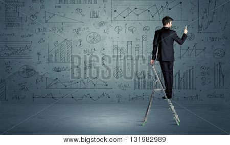 A businessman in modern stylish elegant suit standing on a small ladder and drawing pie and block charts on grey wall background with exponential progressing  lines, circles, angles, blocks, numbers