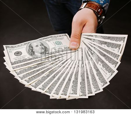 Hand holding money fan. One hundred dollar bills on a gray background. Banknote, close-up. The offer of a bribe