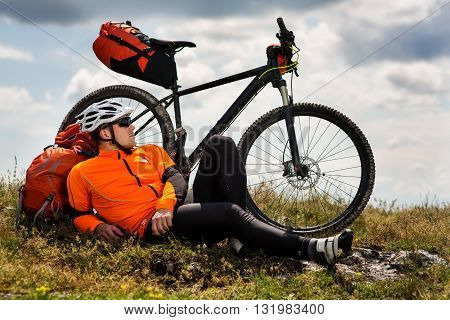 Young man cyclist sitting near the cycle on a green meadow