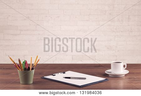 Close up of business office desk with pen board coffee in front of empty white brick textured wall background.