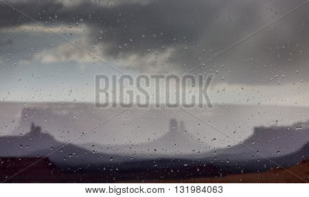 Abstract blurry background: view through the wet window Monument valley usa
