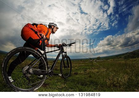 Wide angle. Young man travel on bicycle on a rural road through green meadow against cludy sky