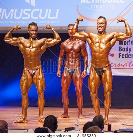 MAASTRICHT THE NETHERLANDS - OCTOBER 25 2015: Male bodybuilders Ali Rezah from Iran with other competitors flex their muscles and show their best physique in a front double biceps pose on stage at the World Grandprix Bodybuilding and Fitness