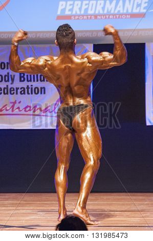 MAASTRICHT THE NETHERLANDS - OCTOBER 25 2015: Male bodybuilder Ali Rezah from Iran flexes his muscles and shows his best physique in a back double biceps pose on stage at the World Grandprix Bodybuilding and Fitness