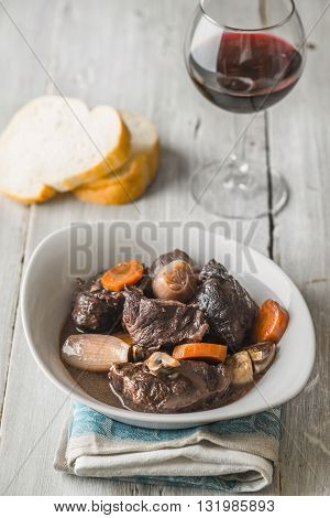 Beef bourguignon in white ceramic plate on a blue towel vertical