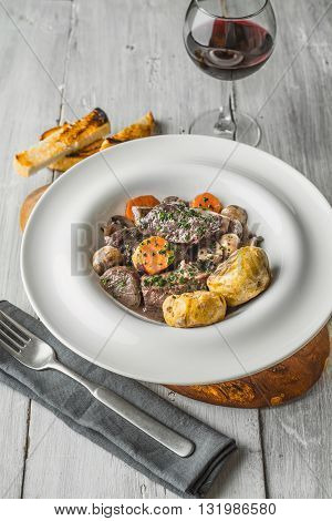 Beef bourguignon in a ceramic dish on stand vertical