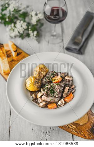 Beef bourguignon in a ceramic dish on a wooden stand vertical