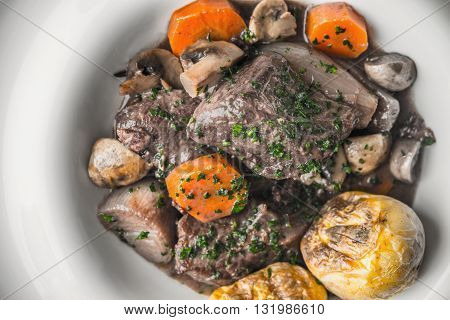 Beef bourguignon in a ceramic plate with grilled potatoes horizontal