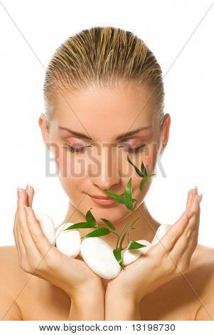 Beautiful blond girl holding young plant growing up through stones