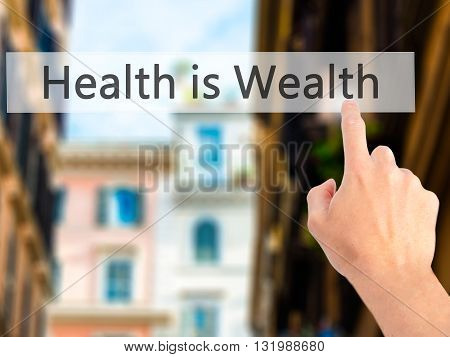 Health Is Wealth - Hand Pressing A Button On Blurred Background Concept On Visual Screen.
