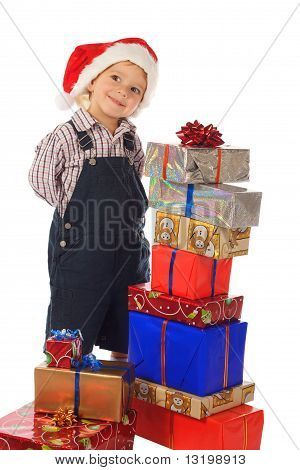 Smiling little boy with Christmas gift boxes