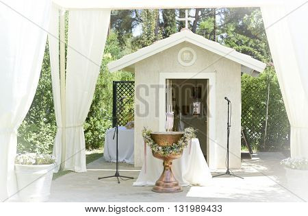 white tent for wedding or entertainment events with a very small chapel and a baptism bowl in a grass field on a sunny summer's day