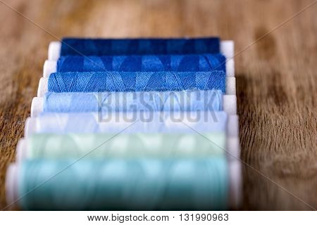cotton sewing in all shades of blue on wood
